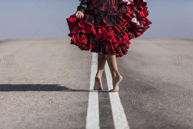 Flamenco dancer walking on an empty road