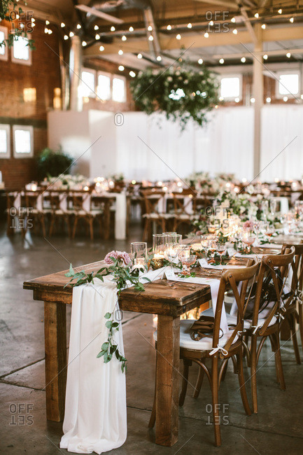 Wooden tables and chairs at a wedding reception