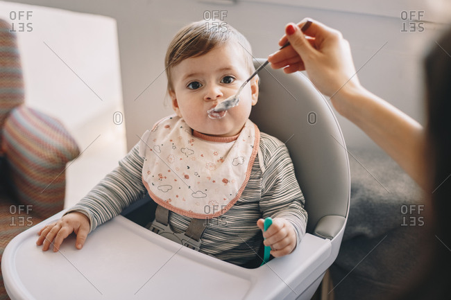 Baby boy being fed with a spoon at home