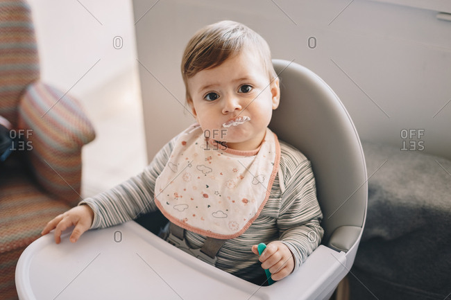 Portrait of an adorable 10 month old baby boy at home, sitting in a feeding chair, waiting for food