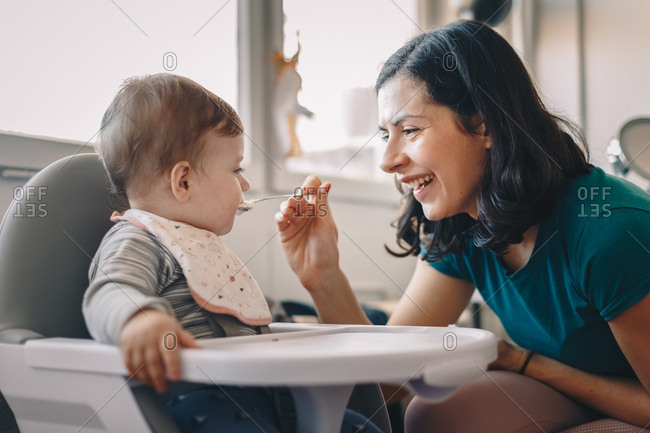 Mother feeding her baby boy breakfast at home