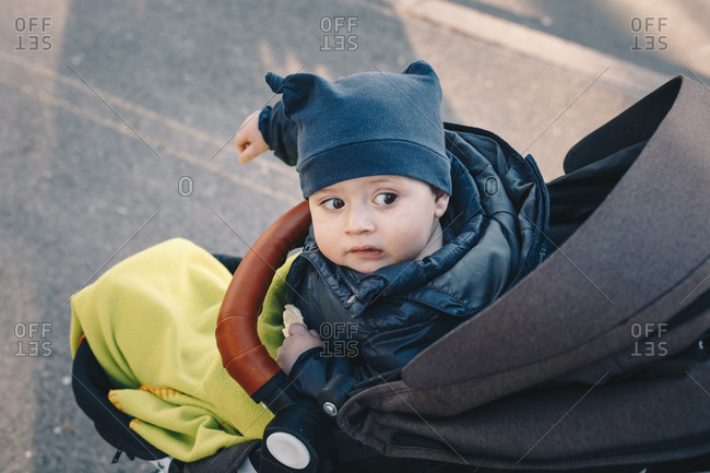 Baby boy  in a stroller outside on a spring day, bundled up and wearing warm clothes