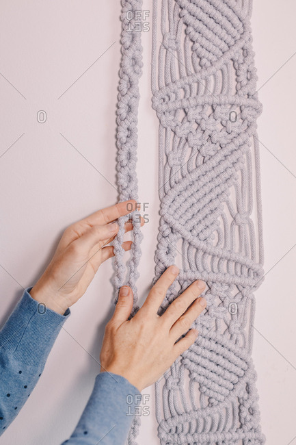 Woman's hands displaying a wall hanging macrame.