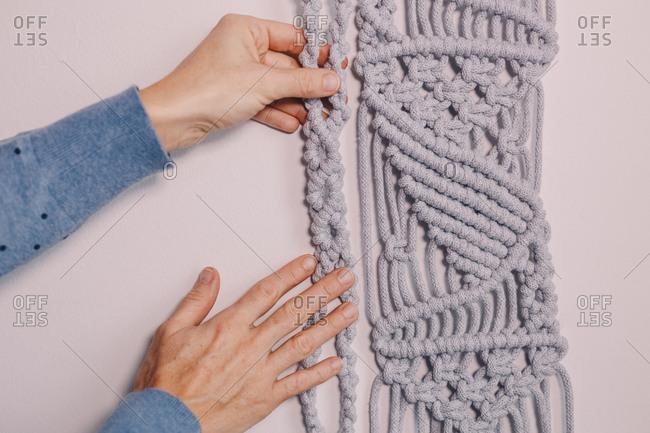 Female hands arranging a wall hanging macrame.