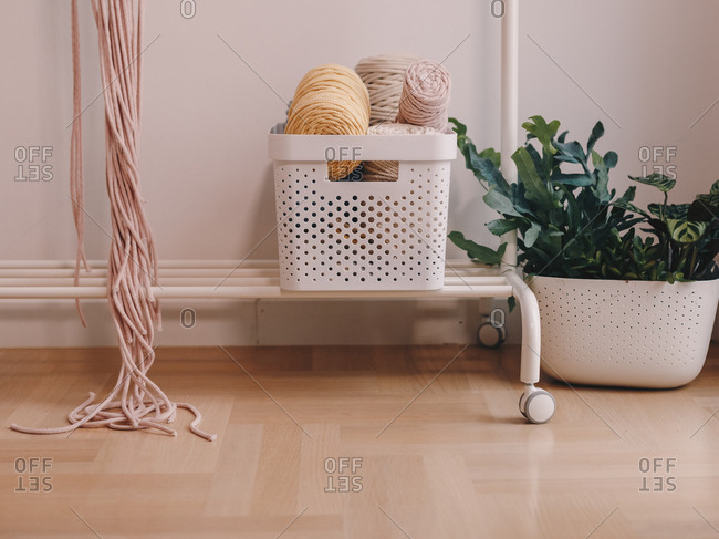 Basket full of yarn balls and other sewing equipment.