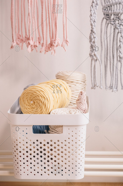 Basket full of yarn clews and other materials used for sewing.