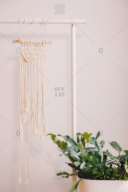 Homemade yellow macrame hanged in a living room space.