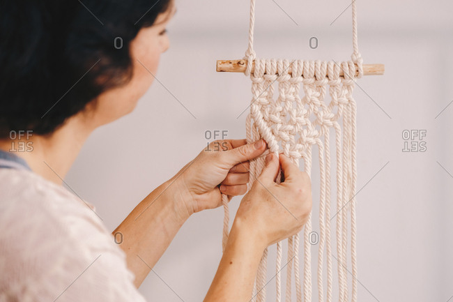 Attractive female entrepreneur and a small business owner, finishing working on a hanging macrame decoration.