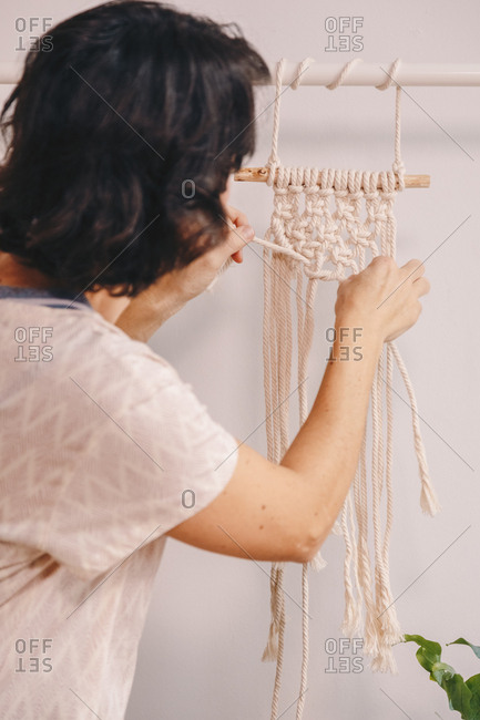 Middle aged small business owner making a hanging macrame.