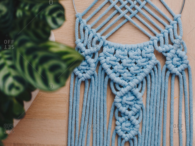 Close up detail of a blue macrame decor on a dream catcher.