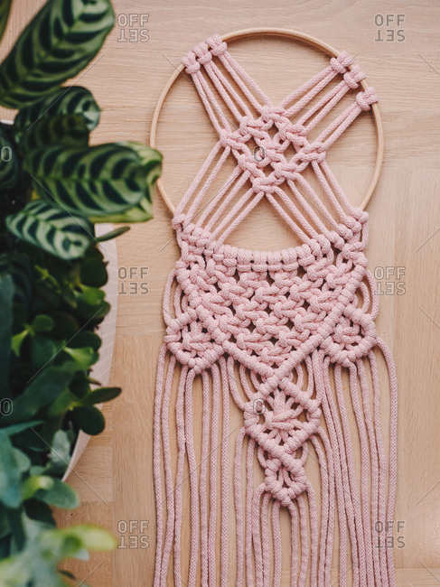 Pink macrame decor on a dream catcher.