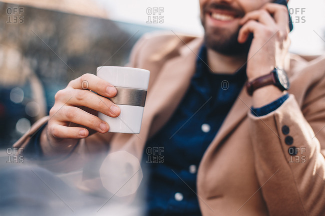 Close up detail shot of fashionable young man wearing a wrist watch and a camel coat, using a mobile phone and holding a white cup of coffee in his hand on a sunny winter day, in an outdoor bar.