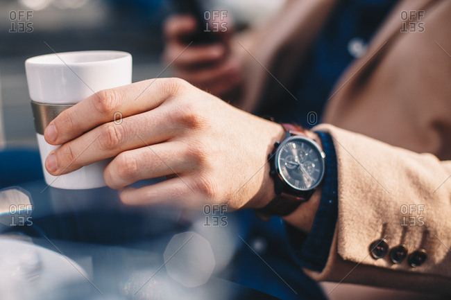 Close up detail shot of stylish young man wearing a wrist watch on his hand, holding a white cup of coffee and using a mobile phone while sitting in an outdoor bar, on a sunny winter day.
