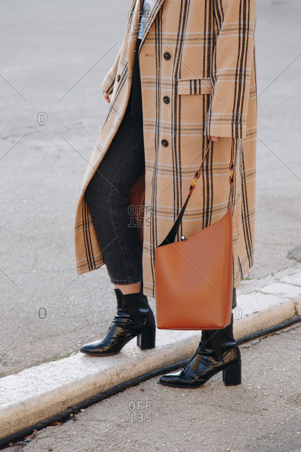 Fashion blogger outfit details. Portrait of young woman in the city, wearing an oversized plaid beige coat, dark jeans, black ankle shoes and a hobo bag.