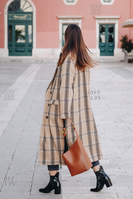 Fashion blogger outfit details. Portrait of young woman wearing oversized plaid beige coat, black ankle boots and hobo bag. Walking on the famous mediterranean square in the city of Split, Croatia.
