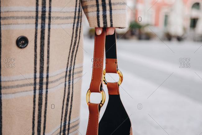 Close up of fashion details. Young fashionable woman's hand holding a bag, wearing a plaid beige coat on a famous mediterranean square.