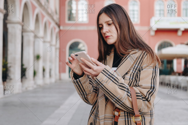 Portrait of young fashion blogger wearing an oversized checked beige coat and a brown hobo bag, while using her mobile phone on the famous mediterranean square in Split, Croatia.