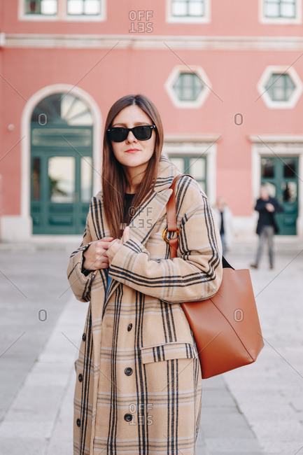 Fashion blogger outfit details. Portrait of young woman wearing an oversized plaid beige coat, sunglasses and a hobo bag. Posing on the mediterranean square in Split, Croatia.