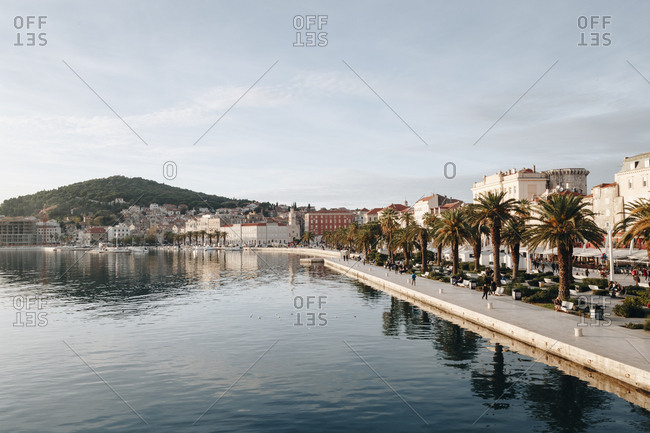 Beautiful scenic view of riva, a famous seaside promenade in the center of Split, Croatia, during daylight. Marjan hill is visible in the distance.