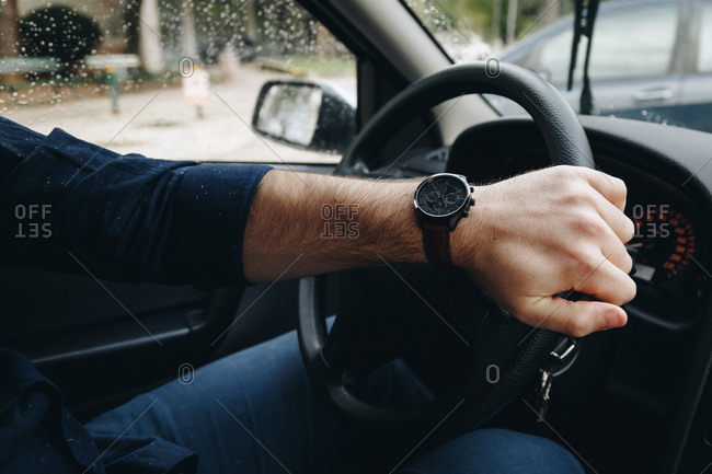 Man's hand holding the steering wheel of a car, wearing a modern wrist watch and making a turn, during a rainy day outside.