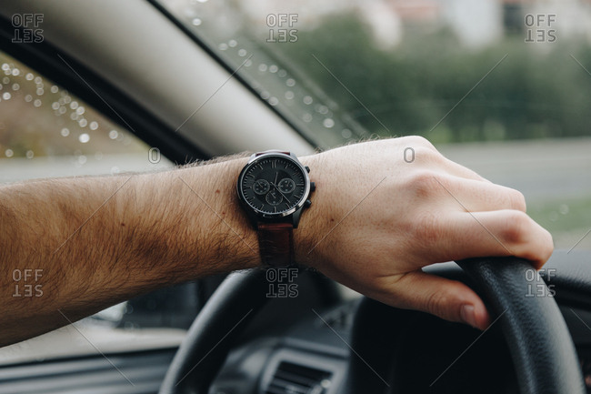 Close up detail of man's hand holding the steering wheel, wearing a modern wrist watch. Rainy day outside.