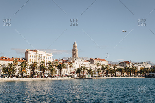 Beautiful scenic view of riva, a famous seaside promenade in the center of Split, Croatia. Cathedral and bell tower of St. Domnius are visible in the distance.