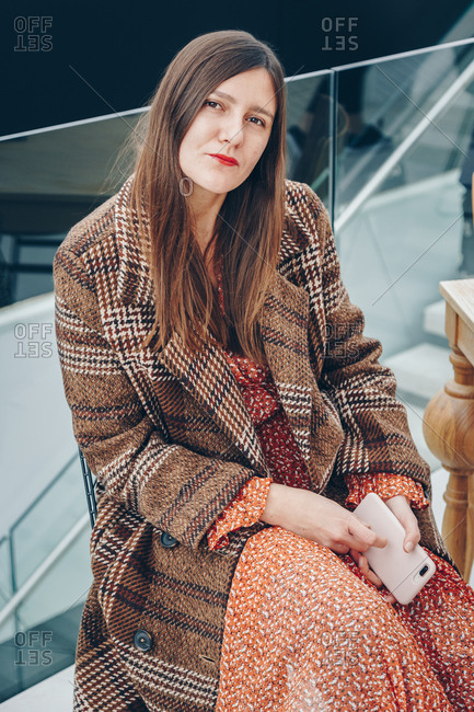 Fashionable young woman sitting in a bar, wearing brown plaid coat and red dot dress, posing and looking at the camera, smiling.