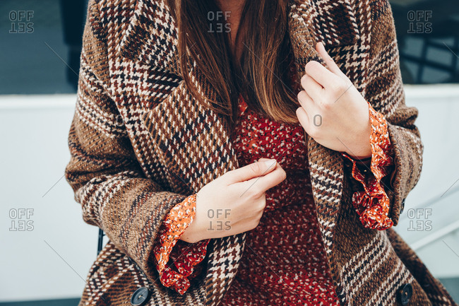 Fashionable young woman's hands straightening brown plaid coat that she's wearing over a red dot dress.
