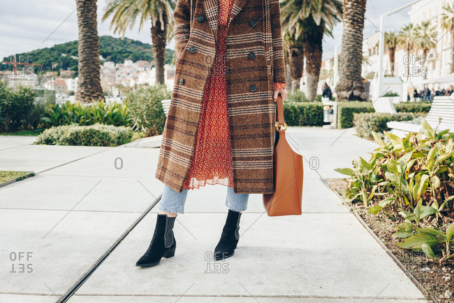 Fashion blogger outfit details. Fashionable woman wearing brown checked oversized coat, red dot dress, regular blue jeans, hobo bag and black suede leather ankle boots. Mediterranean city surrounding.