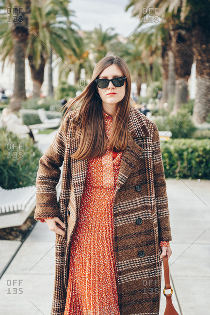 Portrait of attractive young stylish woman wearing plaid overcoat and red dot dress beneath it, posing with sunglasses on a beautiful seaside promenade lined by palm trees. City of Split, Croatia.