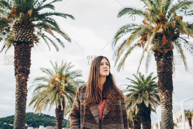 Portrait of hopeful young freelancer wearing oversized checked coat, looking up while standing by the line of palm trees in the mediterranean city of Split, Croatia. Space for copy, text, advertising.