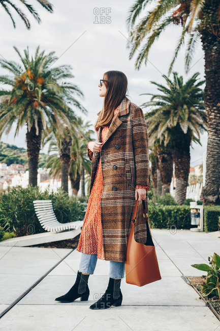 Portrait of attractive casual young blogger wearing plaid overcoat, jeans, red dress, hobo bag and black ankle boots, posing on beautiful waterfront lined by palm trees. City of Split, Croatia.