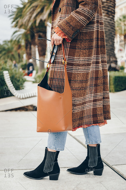Fashion blogger outfit details. Fashionable woman wearing checked oversized coat, red dot dress, regular blue jeans, hobo bag, sunglasses and black suede ankle boots. Mediterranean city surrounding.