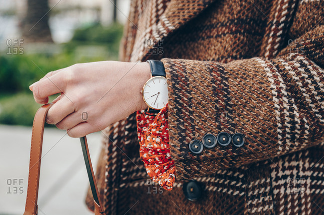 Close up of fashion details. Young fashionable woman holding her bag, wearing a plaid brown coat and a classic hand watch, on a sunny day.