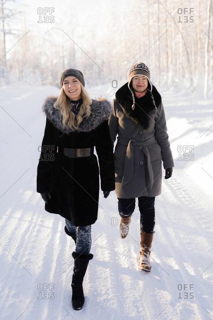 Two women walking in snowy Finnish landscape