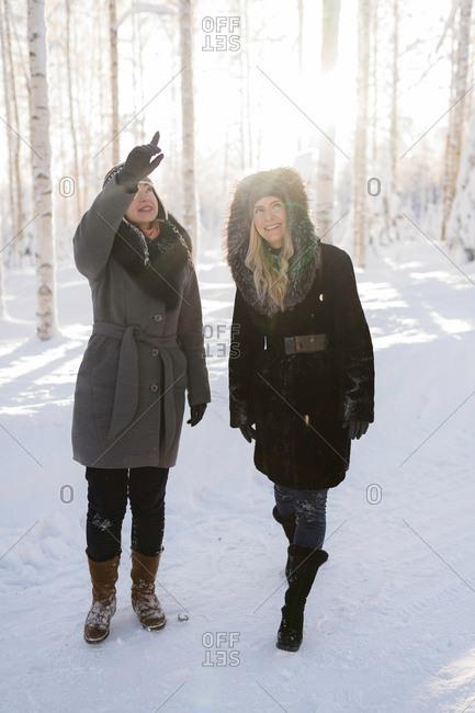 Two women exploring snowy Finnish landscape