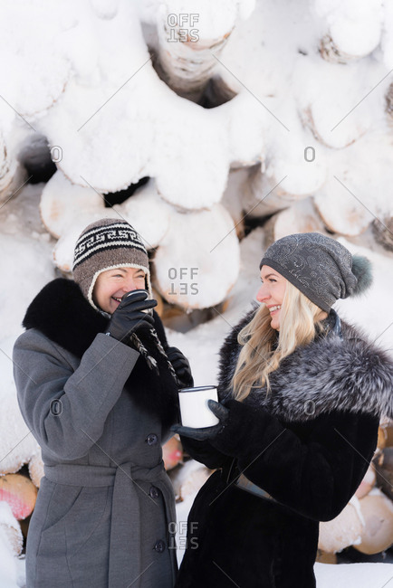 Two women drinking warm beverages in front of snow covered birch logs