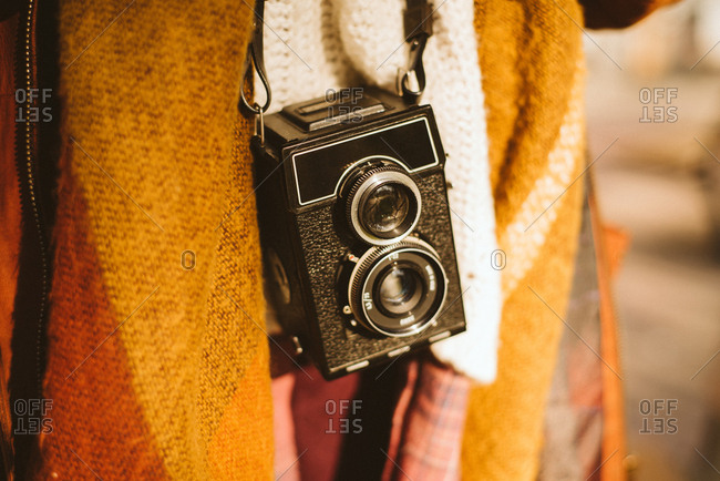 Photographer carrying vintage twin-lens reflex camera