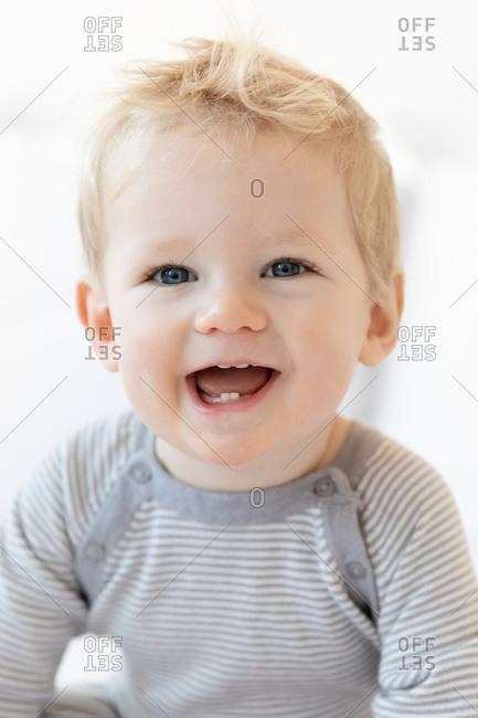Portrait of a cute blonde toddler in a striped onesie