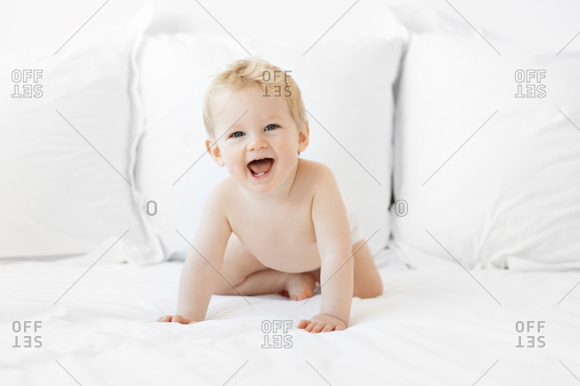 Adorable blonde 2 year old laughing during tummy time