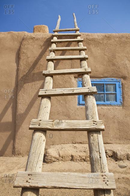 Wooden Ladder Against an Adobe Building
