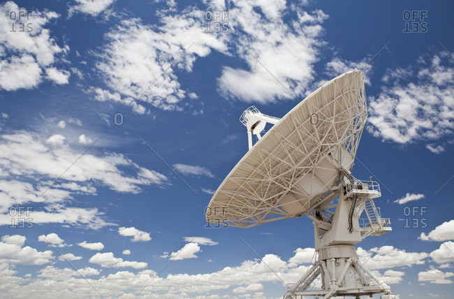Satellite dish under blue sky with clouds