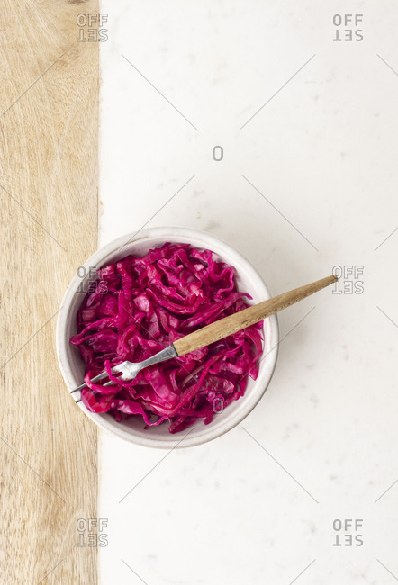 A bowl of sauerkraut with a fork on a marble and wooden board.