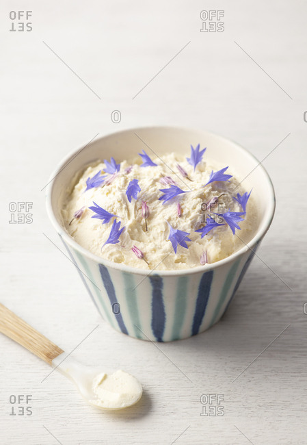 Homemade ricotta topped with edible flowers in a striped bowl with a spoon on a white surface.