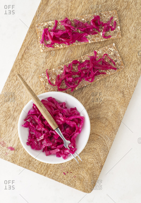 Pink sauerkraut on rye crackers and in a bowl with a fork on a cutting board.