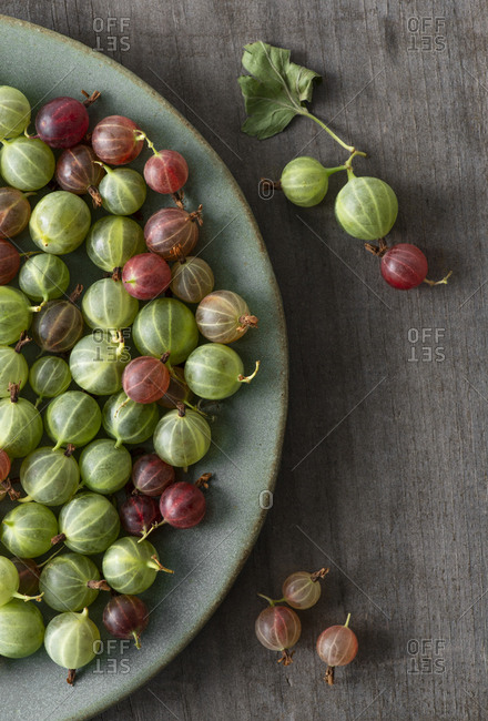 Gooseberries on a ceramic plate on weathered wood.