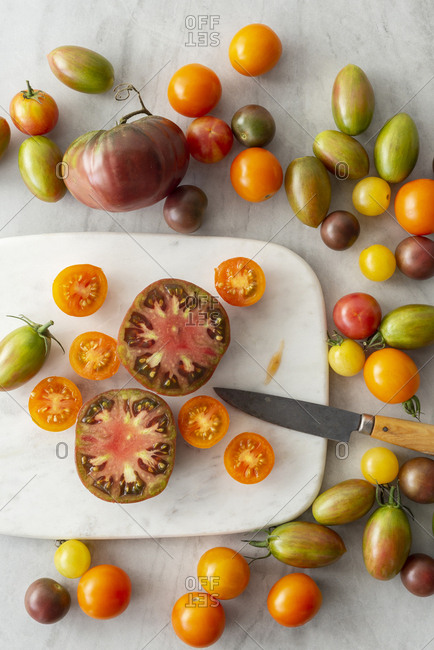 A range of tomato varieties, some cut open, on a marble cutting board with a knife.