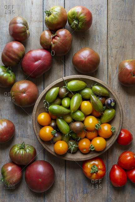 A variety of small and large garden-fresh tomatoes in a wooden bowl on a wooden table.