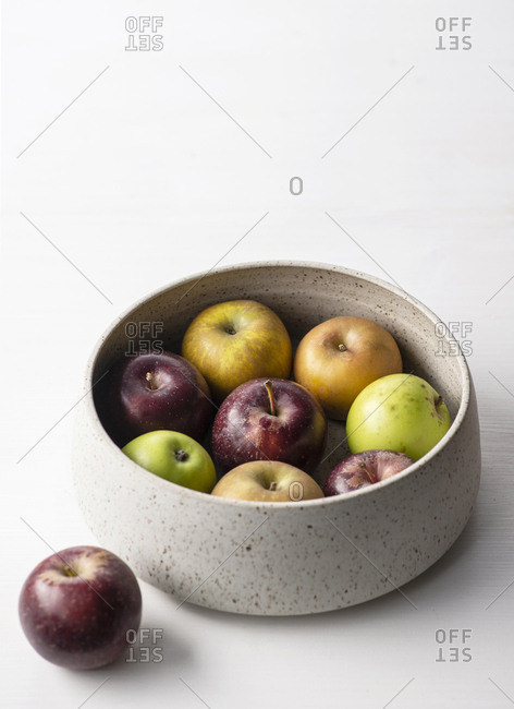 Colorful heirloom apples in a ceramic bowl on a white surface.