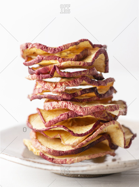 A stack of dried apples on a ceramic plate.